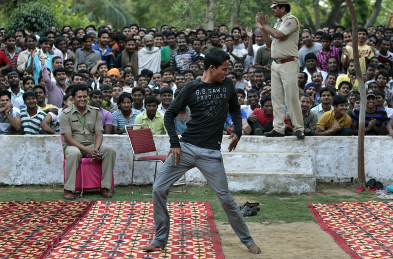 FILE – In this April 26, 2012 file photo, an inmate of Tihar jail, the largest complex of prisons in south Asia, dances during a musical evening for inmates in New Delhi, India. India's Tihar Jail is a land of bakeries and carpentry shops, where inmates compete in music contests, take classes and perform intensive Buddhist meditation as part of their rehabilitation. Tihar Jail is also a vast, overcrowded facility, crammed with people awaiting trial who sleep on concrete floors, face daily threats from other prisoners and are shaken down for bribes from their poorly paid jailers, according to human rights lawyers and former inmates there. The two sides of India's most famous jail emerged this week when a man accused in the notorious rape of a woman aboard a New Delhi bus was found dead in his cell, Monday, March 11, 2013, either a suicide, according to jail officials, or a victim of foul play, according to his family. (AP Photo/Saurabh Das, File)