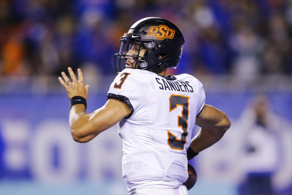 Oklahoma State quarterback Spencer Sanders looks for a recever during the first half of the team's NCAA college football game against Boise State on Saturday, Sept. 18, 2021, in Boise, Idaho. (AP Photo/Steve Conner)
