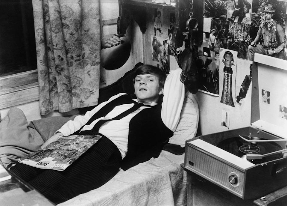"""MALCOLM MCDOWELL LIES ON BED LISTENING LISTENING TO HI-FI STARRING IN THE 1968 PARAMOUNT FILM """"IF"""". FILM PHOTO. (Photo by �� John Springer Collection/CORBIS/Corbis via Getty Images)"""