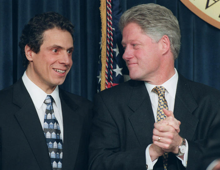 FILE — In this Dec. 20, 1996 file photo, Housing Secretary-designate Andrew Cuomo looks on as President Clinton applauds during a news conference in the Old Executive Office Building in Washington, where the president announced Cuomo's, and other selections, for his administration in his second term. Cuomo got his start in politics as his father's aide and campaign manager, before serving as U.S. housing secretary under Bill Clinton and state attorney general. (AP Photo/Denis Paquin File)
