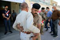 Security forces search people outside a polling station during parliamentary elections in Basra, Iraq, Sunday, Oct. 10, 2021. Iraq closed its airspace and land border crossings on Sunday as voters headed to the polls to elect a parliament that many hope will deliver much needed reforms after decades of conflict and mismanagement. (AP Photo/Nabil al-Jurani)