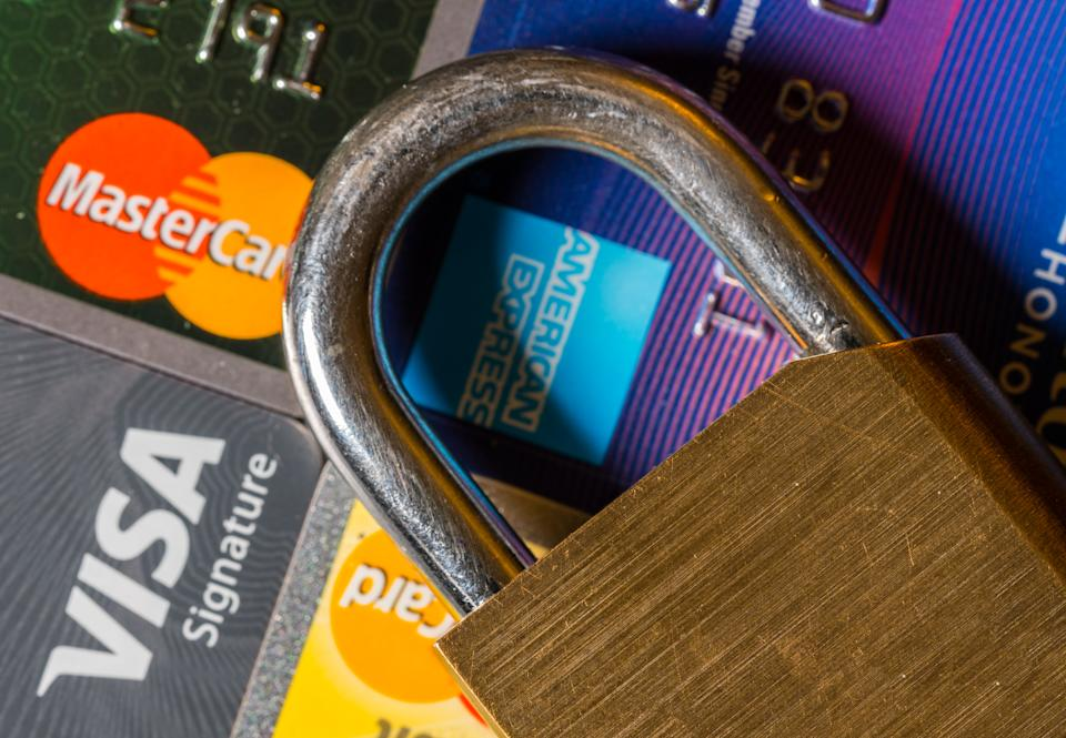 MORGANTOWN, WV - 9 AUGUST 2018: Padlock on credit cards from various issuers with focus on lock
