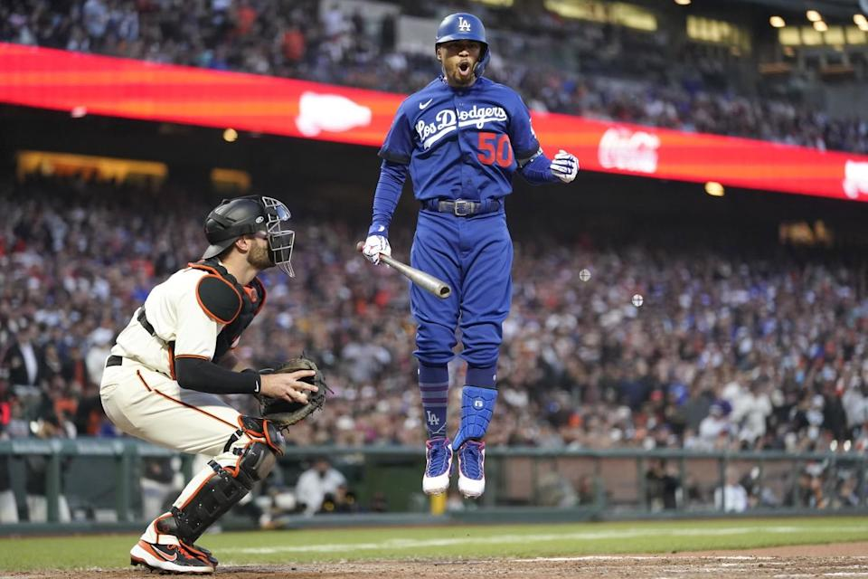 A Dodgers player jumps in the air in the batter's box