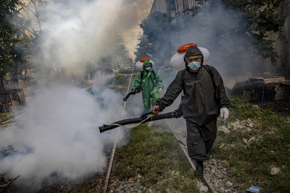 Workers wearing a hazmat suits disinfect a slum community along a railway as preventive measure against COVID-19 on March 26, 2021 in Manila, Philippines. Curfews and stricter lockdowns are being implemented in several areas across the Philippines as the country experiences its worst surge in cases since the lockdown began more than a year ago. The country has reported more than 693,000 cases of COVID-19 so far, with at least 13,095 deaths. (Photo: Ezra Acayan/Getty Images)