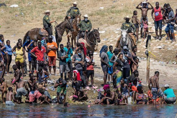 PHOTO: Border Patrol agents watch Haitian immigrants on the bank of the Rio Grande in Del Rio, Texas, Sept. 20, 2021, as seen from Ciudad Acuna, Mexico. (John Moore/Getty Images)