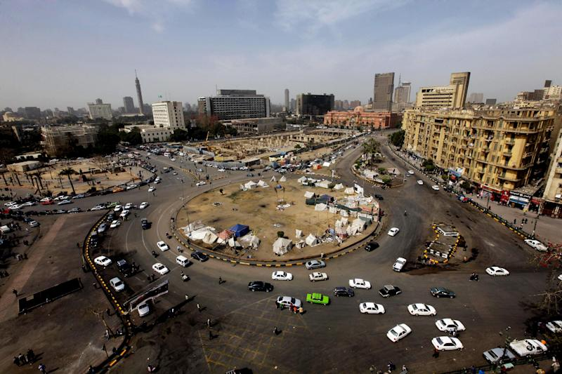 Vehicles pass through Tahrir Square, the focal point of the 2011 Egyptian revolution, for the first time in months, in Cairo, Egypt, Sunday, March 3, 2013. Security forces re-opened Tahrir Square removing barbed wire across the entrances to allow traffic to flow normally. Protesters have held a sit-in in the square since Nov. 22, 2013 after President Morsi issued a controversial constitutional declaration that rendered his decisions above judicial supervision. (AP Photo/Amr Nabil)