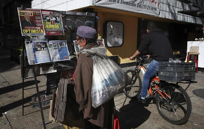 A man reads the front pages of newspapers showing the news that Mexican President Andrés Manuel López Obrador has COVID-19, at a kiosk on Paseo de la Reforma in Mexico City, Monday, Jan. 25, 2021. López Obrador was working from isolation on Monday, Jan. 25, 2021, a day after announcing that he had tested positive for COVID-19, his interior secretary said. (AP Photo/Marco Ugarte)