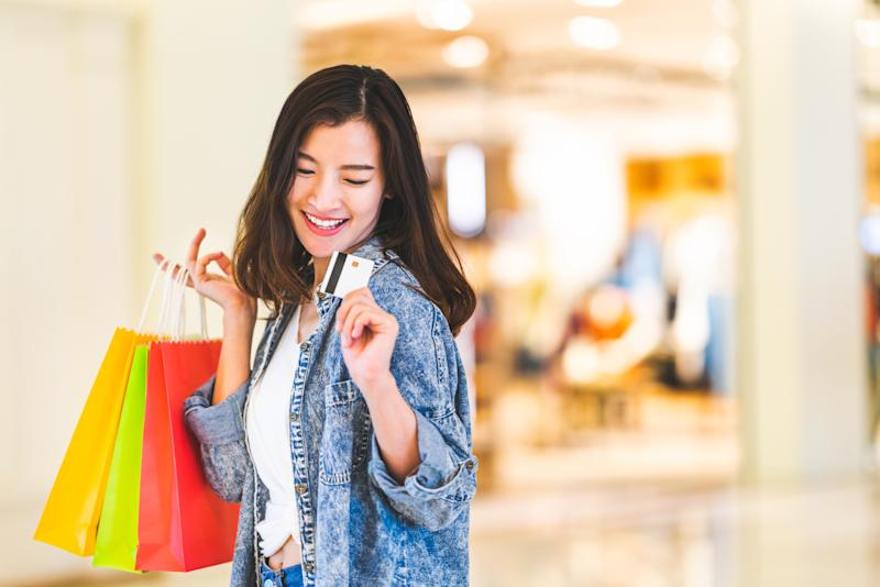 Woman happily wielding credit card while shopping