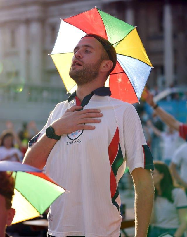 An England fan in a novelty umbrella hat sings the national anthem in Trafalgar Square