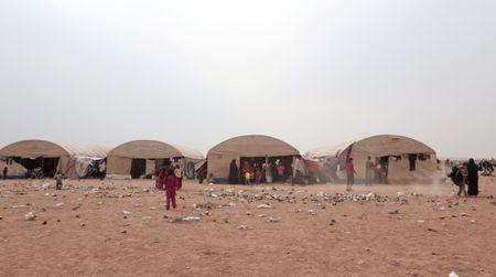 Iraqi refugees who fled the violence in Mosul walk past tents near the Iraqi border, in Hasaka Governorate, Syria
