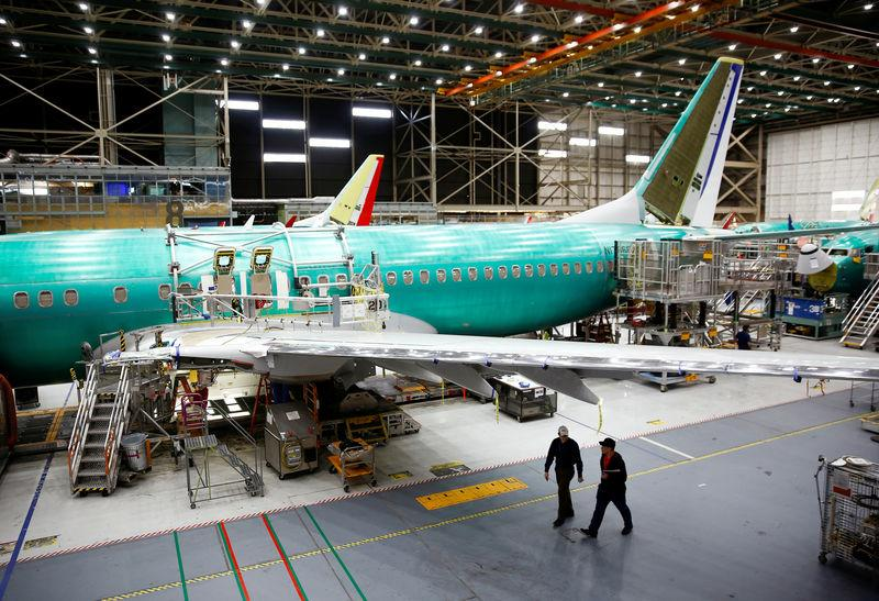 Two workers walk under the wing of a 737 Max aircraft at the Boeing factory in Renton