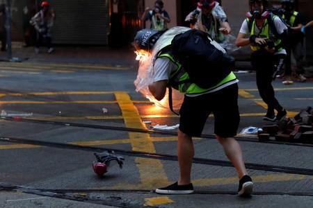 A member of the press reacts after being hit with a molotov cocktail during an anti-government rally in central Hong Kong