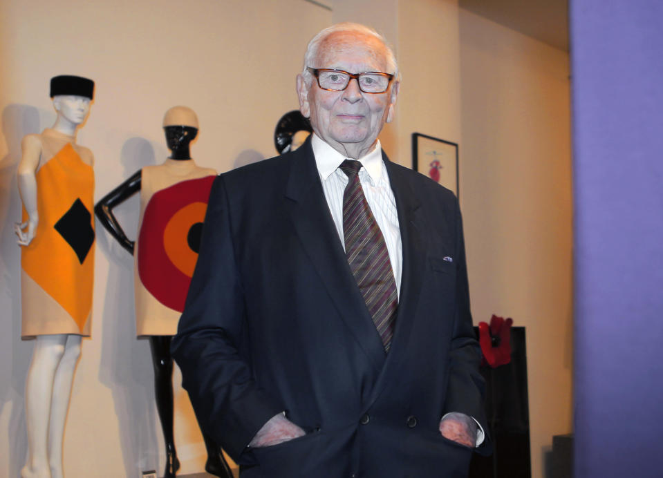 FILE - In this file photo dated Thursday, Nov. 13, 2014, French fashion designer Pierre Cardin poses backdropped by some of his designs during the inauguration of the Pierre Cardin Museum in Paris, France. France's Academy of Fine Arts said Tuesday Dec. 29, 2020, that famed fashion designer Pierre Cardin has died aged 98. (AP Photo/Jacques Brinon, FILE)