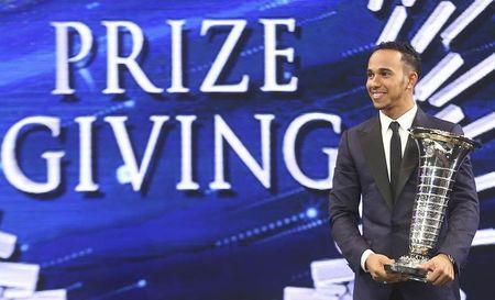 Mercedes Formula One World Champion Lewis Hamilton of Britain holds his trophy during the 2014 International Automobile Federation (FIA) Gala Prize-Giving ceremony in Doha December 5, 2014. REUTERS/Fadi Al-Assaad