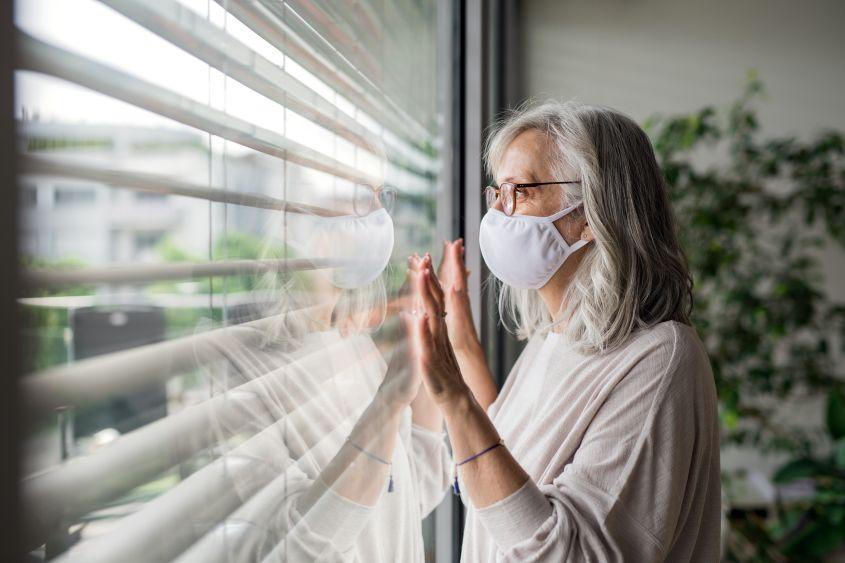 Woman with face mask standing indoors by window at home.