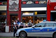 Police stand outside where a 21-year-old Syrian refugee killed a woman with a machete and injured two other people in the city of Reutlingen, Germany July 24, 2016. REUTERS/Vincent Kessler