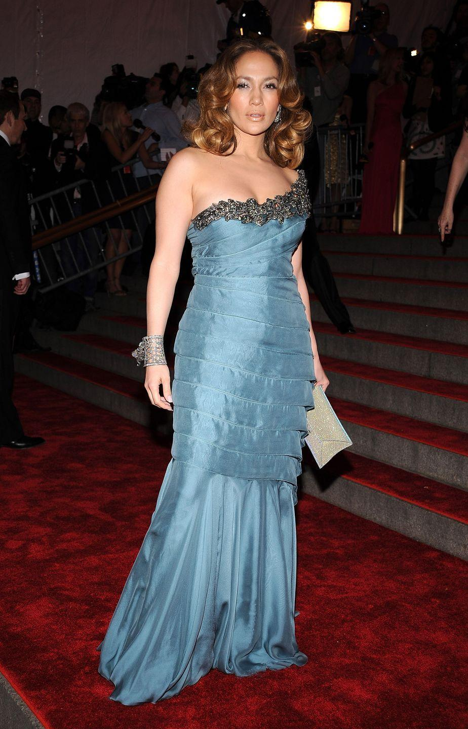 <p>Can we just take a moment to take in how much Met Gala fashion has changed?! Here, J.Lo wears a tiered, one-shoulder Armani dress with a bejeweled neckline and a statement bangle.</p>