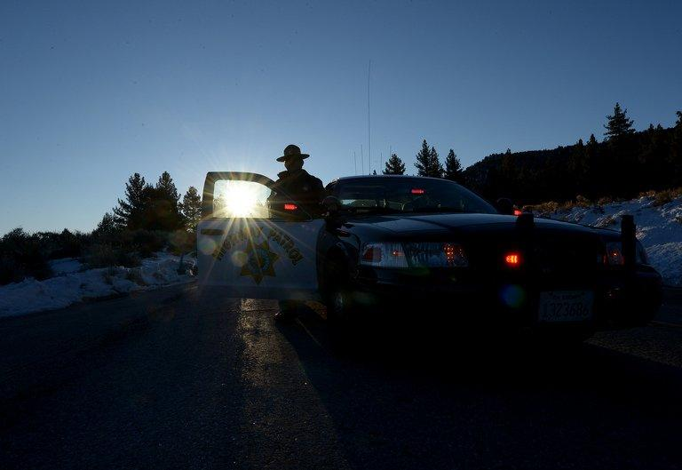 A California Highway Patrol officer guards a roadblock in the San Bernardino Mountains, on February 13, 2013