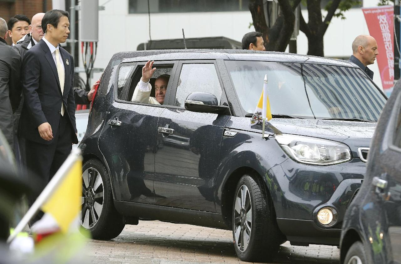 "Pope Francis waves from a car after celebrating a Mass for peace and reconciliation outside Myeong-dong cathedral in Seoul, South Korea, Monday, Aug. 18, 2014. Pope Francis wrapped up his first trip to Asia on Monday by challenging Koreans - from the North and the South - to reject the ""mindset of suspicion and confrontation"" that cloud their relations and instead find new ways to forge peace on the war-divided peninsula. (AP Photo/Ahn Young-joon)"
