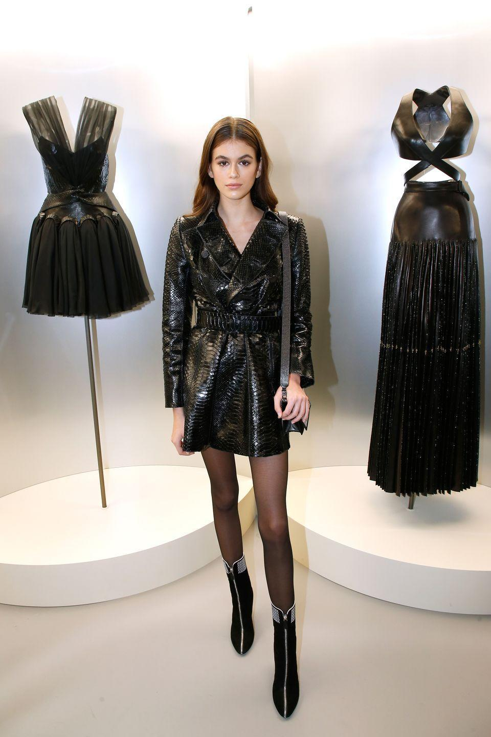 <p>The model-of-the-moment worked Parisian chic at the 'Azzedine Alaia : Je Suis Couturier' exhibition as part of Paris Fashion Week. She paired sheer tights, black high-heeled boots and a black chain bag with an alligator-textured coat dress. </p>