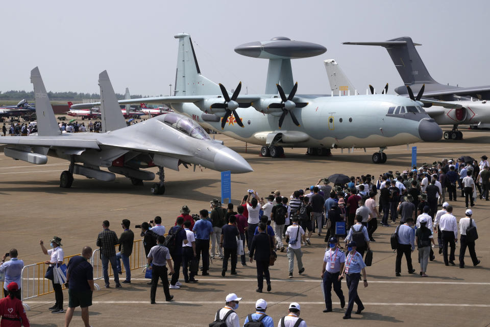 Visitors view the Chinese military's J-16D electronic warfare airplane, left, and the KJ-500 airborne early warning and control aircraft at right during 13th China International Aviation and Aerospace Exhibition, also known as Airshow China 2021, Wednesday, Sept. 29, 2021, in Zhuhai in southern China's Guangdong province. With record numbers of military flights near Taiwan over the last week, China has been stepping up its harassment of the island it claims as its own, showing an new intensity and sophistication as it asserts its territorial claims in the region. (AP Photo/Ng Han Guan)