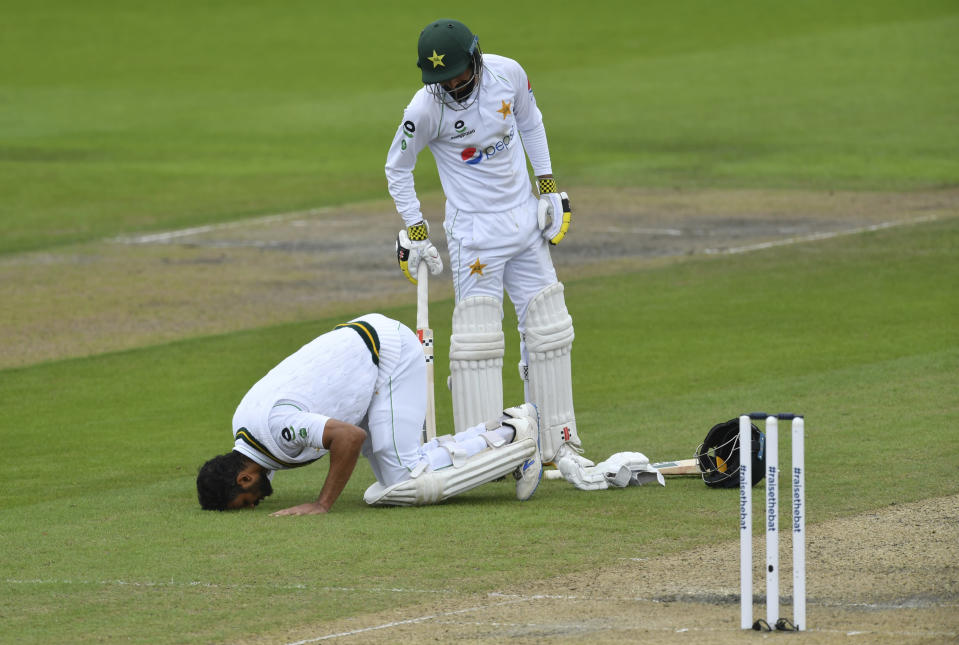 Pakistan's Shan Masood, left, celebrates after scoring a century during the second day of the first cricket Test match between England and Pakistan at Old Trafford in Manchester, England, Thursday, Aug. 6, 2020. (Dan Mullan/Pool via AP)