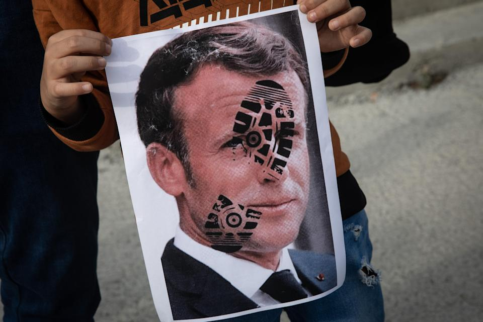 A protester holds up an image of Emmanuel Macron during demonstrations in Istanbul on Sunday (Getty Images)