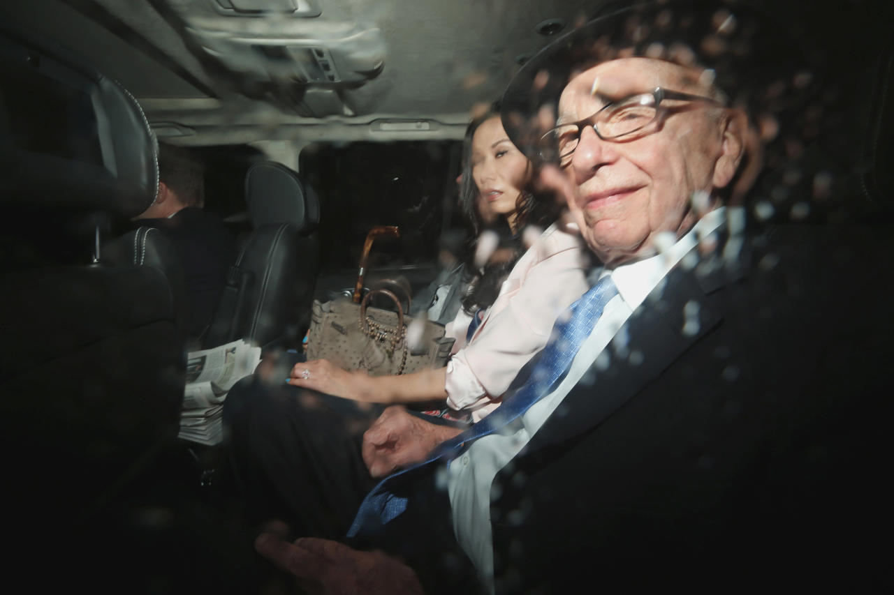 News Corp. chairman Rupert Murdoch, right, and his wife Wendi Deng sit in the back of a car as they are driven to the Leveson inquiry at the High Court in London, Thursday, April 26, 2012. (AP Photo/Matt Dunham)