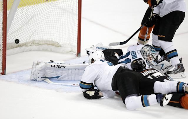 Anaheim Ducks' Nick Bonino(13) and San Jose Sharks' Brad Stuart(7) fall to the ice after Bonino scored against San Jose Sharks goalie Antti Niemi(31), of Finland, during the second period of an NHL hockey game on Tuesday, Dec. 31, 2013, in Anaheim, Calif. (AP Photo/Jae C. Hong)
