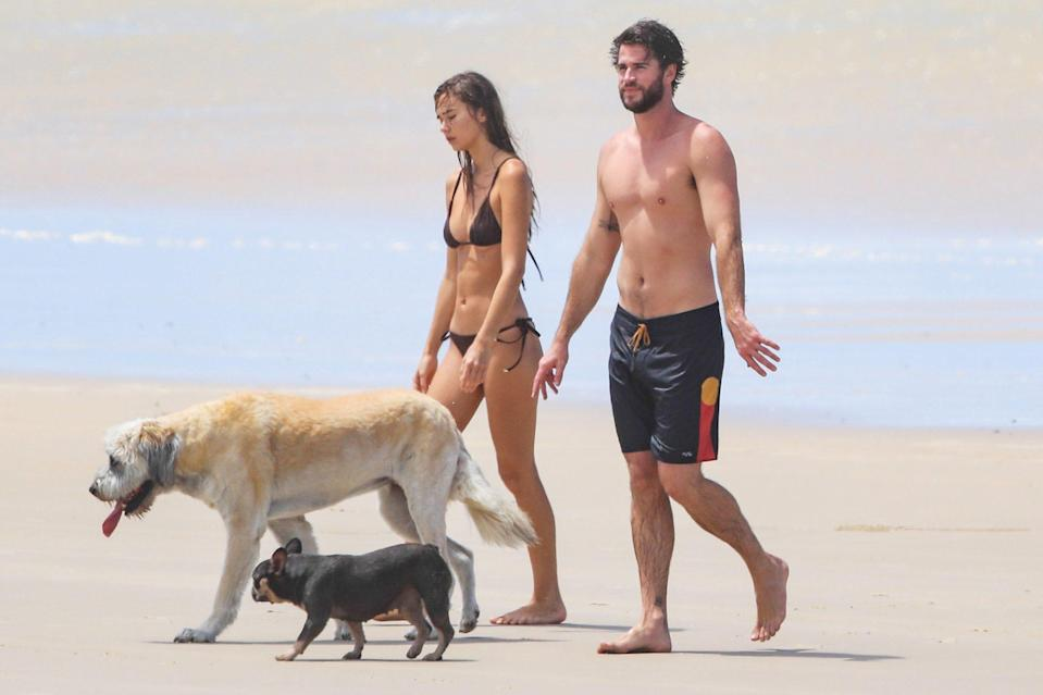 <p>Liam Hemsworth and girlfriend Gabriella Brooks take their dogs out for a walk on the beach in Australia on Wednesday.</p>