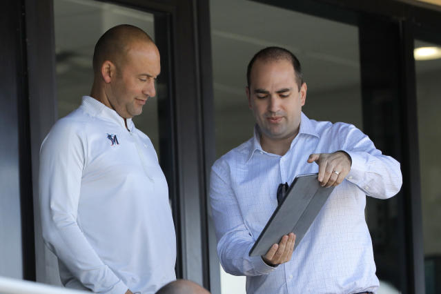 Miami Marlins CRO Adam Jones, right, shows a tablet to Marlins CEO Derek Jeter during the eighth inning of a spring training baseball game between the Washington Nationals and the Marlins, Tuesday, March 10, 2020, in Jupiter, Fla. (AP Photo/Julio Cortez)