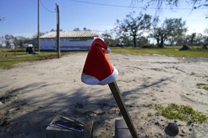 A Santa hat sits on a pole on a lot where Dewana Young's mother's home once stood before Hurricane Laura and Hurricane Delta, in Grand Lake, La., Friday, Dec. 4, 2020. (AP Photo/Gerald Herbert)