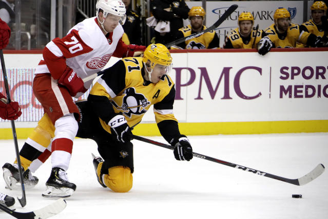 Pittsburgh Penguins' Evgeni Malkin (71) gets off a pass as he falls to the ice with Detroit Red Wings' Christoffer Ehn (70) defending during the second period of an NHL hockey game in Pittsburgh, Thursday, Dec. 27, 2018. (AP Photo/Gene J. Puskar)