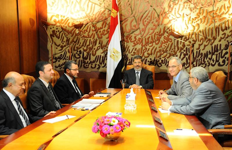 """FILE - In this Monday, July 1, 2013 file photo released by the office of the Egyptian Presidency, Mohammed Morsi, center, meets with members of his government leadership in Cairo, Egypt. """"Over my dead body!"""" Mohammed Morsi told his army chief who came to him asking the Islamist president to step down on his own and not resist a military ultimatum and the demands of giant crowds out in the streets. Morsi found himself isolated, with trusted aides abandoning him, and in the end, the ring of Presidential Guards protecting him simply stepped away to allow the military to take him under its custody, according to army, security and Brotherhood officials giving The Associated Press an account of his last hours.(AP Photo/Egyptian Presidency)"""