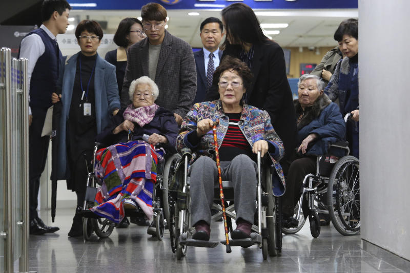Former South Korean comfort women, Lee Yong-soo, center, Lee Ok-seon and Gil Won-ok, right, leave the Seoul Central District Court in Seoul, South Korea, Wednesday, Nov. 13, 2019. A Seoul court on Wednesday began hearing a long-awaited civil case filed against the Japanese government by South Korean women who were forced to work in Japan's World War II military brothels. (AP Photo/Ahn Young-joon)