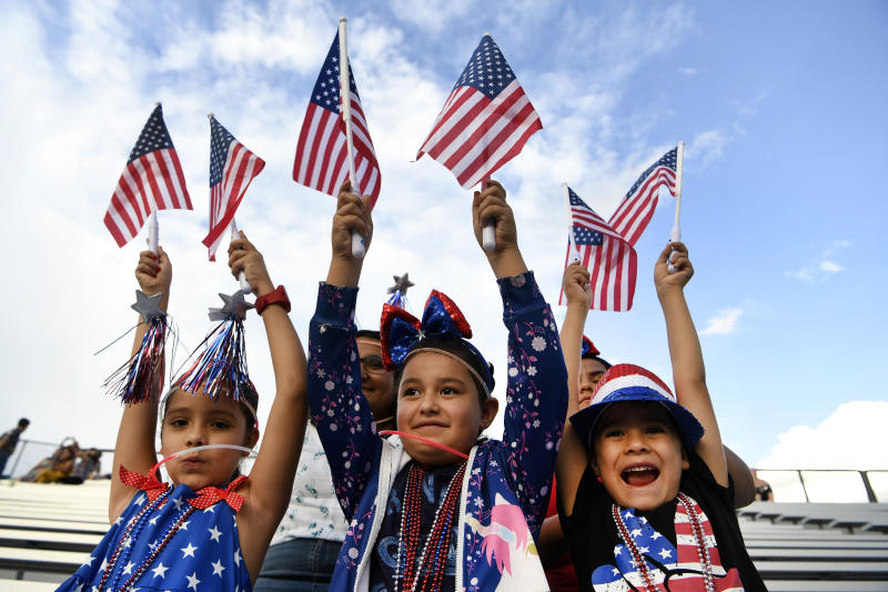 Sadie Portillo, 7, left, her brother Santos, 6, right, and their cousin Adrienne Jaramillo, 6, wave American flags and came dressed to celebrate the Fourth of July and watch the fireworks display with their family at JeffCo stadium on July 4, 2019 in Lakewood, Colorado. (Photo: Helen H. Richardson/MediaNews Group/The Denver Post via Getty Images)