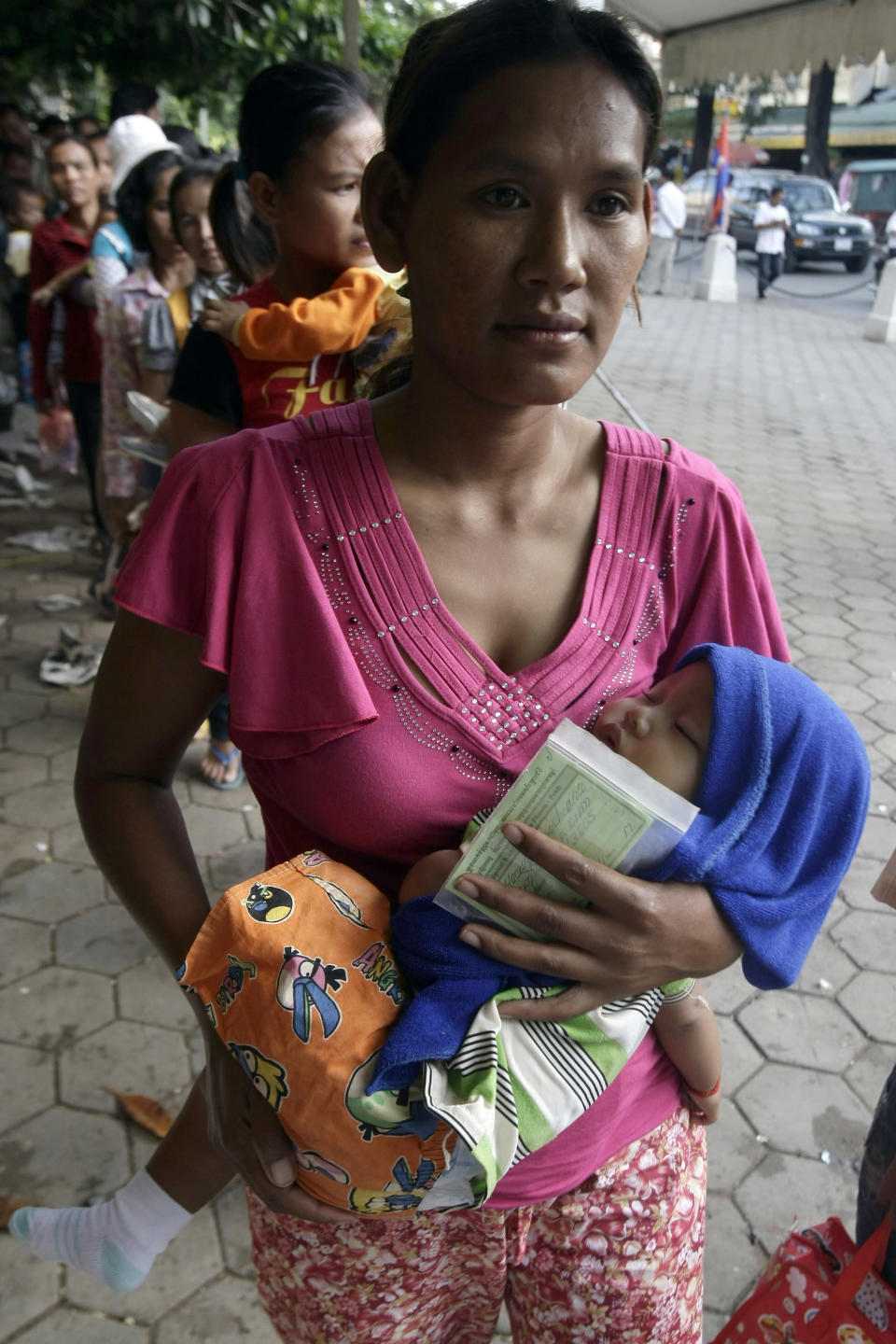 A Cambodian lines up to wait for a medical check-up for her baby outside Kuntha Bopha children's hospital in Phnom Penh, Cambodia, Wednesday, July 11, 2012. The enterovirus 71 strain, or EV-71, raised fears earlier this week after it was detected in some lab samples taken after 52 of 59 Cambodian children died suddenly from a mystery illness that sparked international alarm. Health officials are still investigating, but say the virus is likely to blame. (AP Photo/Heng Sinith)