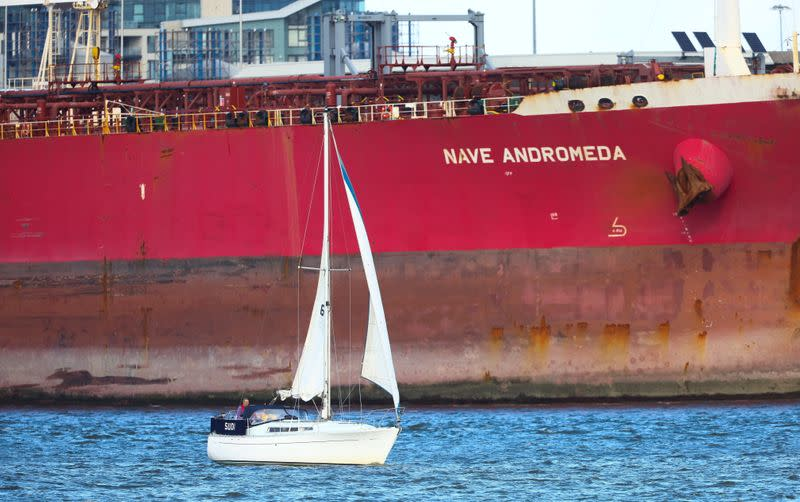 A sailboat passes in front of the Liberia-flagged oil tanker Nave Andromeda at Southampton Docks, following a security incident aboard the ship the night before off the coast of Isle of Wight, in Southampton