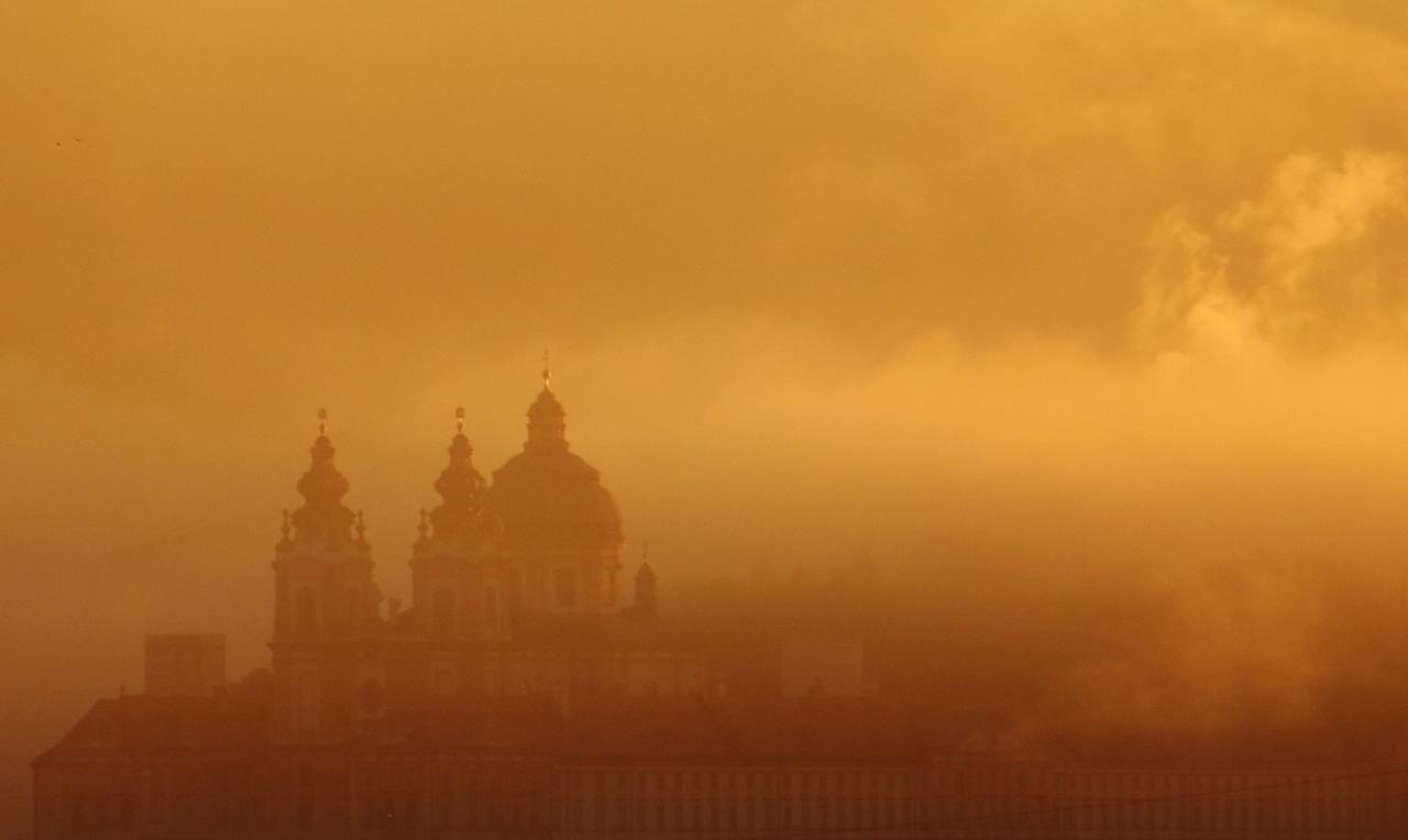 Melk Abbey is pictured through mist in the morning sun in Melk