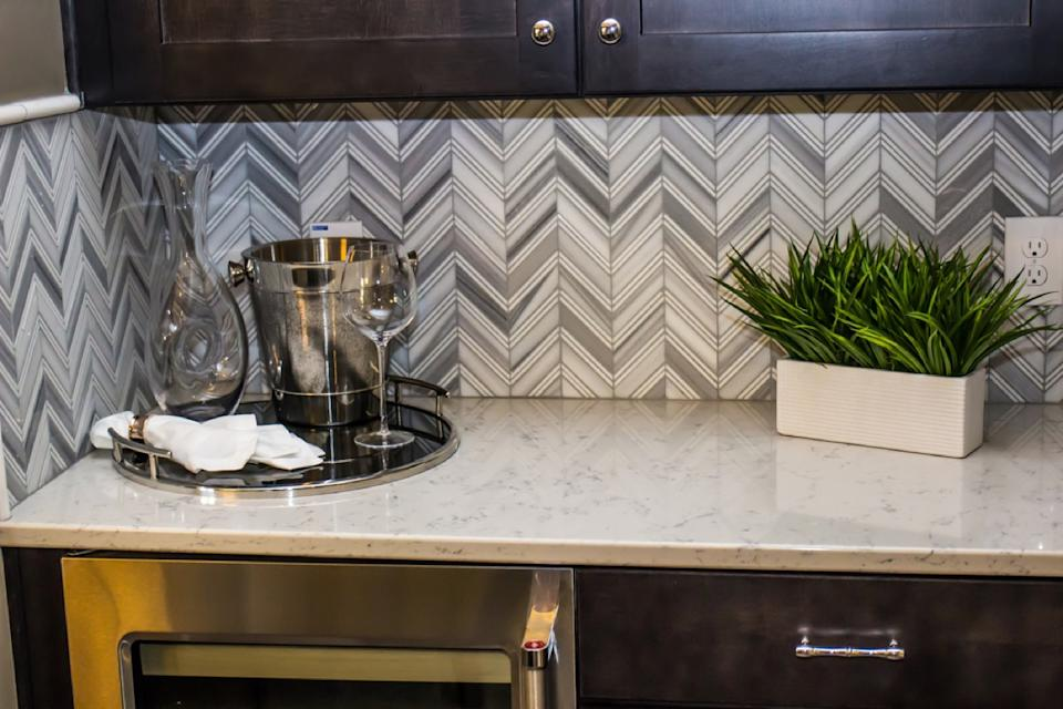 modern kitchen with dark cabinetry, white stone counters, and gray chevron backsplash