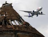 A FedEx plane flies over a former pigeon house. The runways for the Charles de Gaulle airport is just two miles away from the village. (Reuters)