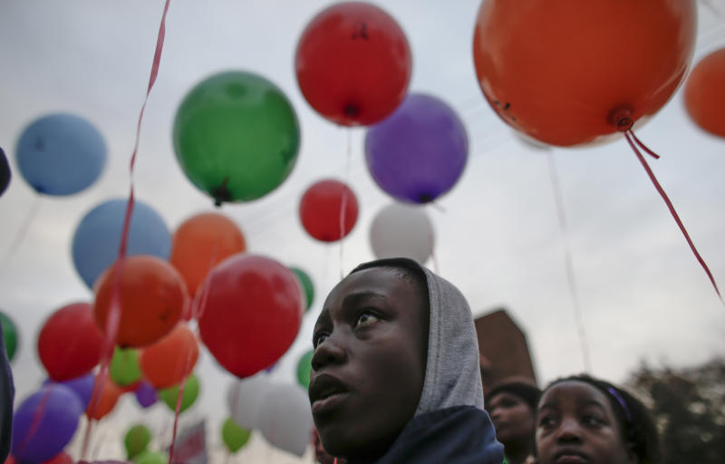 """Children and other well-wishers release balloons to mark former South African President Nelson Mandela completing his 27th day in hospital Thursday, correlating with the 27 years he spent in prison during the apartheid era, outside the Mediclinic Heart Hospital where he is being treated in Pretoria, South Africa Friday, July 5, 2013. The former president's health is """"perilous,"""" according to documents filed in the court case that resulted in the remains of his three deceased children being reburied Thursday in their original graves. (AP Photo/Markus Schreiber)"""