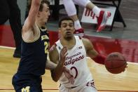 Wisconsin's D'Mitrik Trice drives past Michigan's Franz Wagner during the second half of an NCAA college basketball game Sunday, Feb. 14, 2021, in Madison, Wis. (AP Photo/Morry Gash)