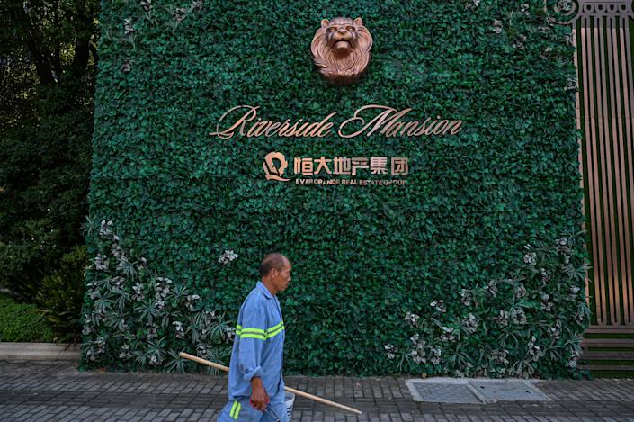 A man walks past a residential building developed by Evergrande in Pudong district in Shanghai on September 22, 2021. (Photo by Hector RETAMAL / AFP) (Photo by HECTOR RETAMAL/AFP via Getty Images)