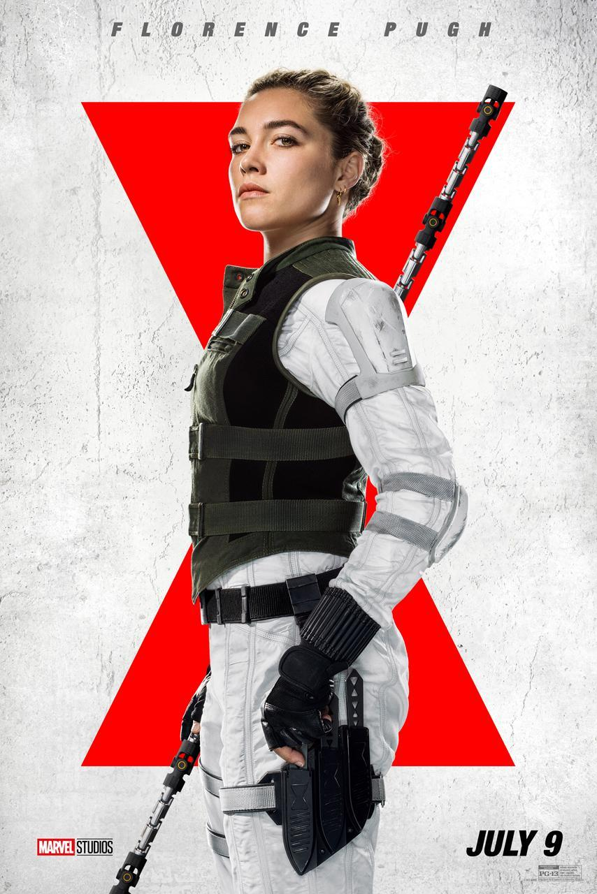 Florence Pugh wears a white suit and black bullet-proof vest, and holds a large staff.