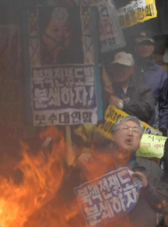 SEOUL, SOUTH KOREA - APRIL 15: South Korean conservative protesters burn a mockup of a North Korean missile and effigies of North Korea national founder Kim Il-Sung, former North Korean leader Kim Jong-Il and now leader Kim Jong-Un during an anti-North Korea rally on April 15, 2013 in Seoul, South Korea. North Korea marks its founder Kim Il-Sung's 101th birthday today while the fear on possible missile launch continues. (Photo by Chung Sung-Jun/Getty Images)
