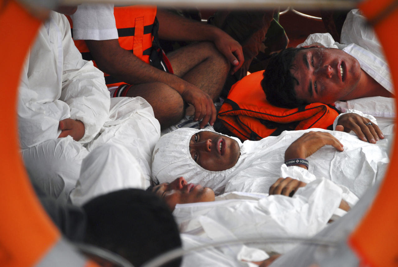 Survivors from a boat reportedly carrying about 150 asylum seekers that sank off Java island, lie on the deck of a rescue boat upon arrival at a port in Merak, Banten province, Indonesia, Friday, Aug. 31, 2012. The wooden fishing boat sank as it headed for a remote Australian island. More than 50 people had been rescued by Friday morning, and one body had been recovered, Australian and Indonesian officials said. (AP Photo)