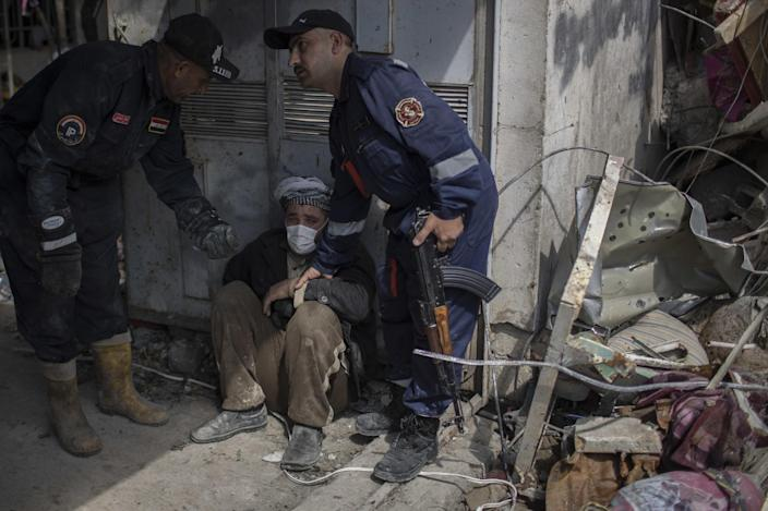 A man is helped after identifying the body of a relative who died in a house that was destroyed during fights between Iraq security forces and the Islamic State. (Photo: Felipe Dana/AP)