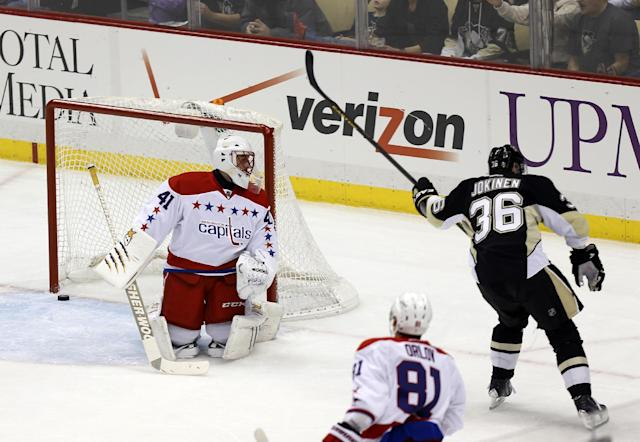 Pittsburgh Penguins' Jussi Jokinen (36), of Finland, celebrates after scoring on Washington Capitals goalie Jaroslav Halak (41), of Slovakia, during the first period of an NHL hockey game, Tuesday, March 11, 2014, in Pittsburgh. (AP Photo/Keith Srakocic)