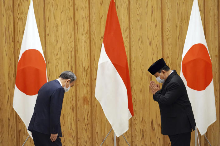 Indonesian Defense Minister Prabowo Subianto, right, and Japan's Prime Minister Yoshihide Suga greet each other during a courtesy call at the prime minister's official residence in Tokyo Tuesday, March 30, 2021. Prabowo and Indonesian Foreign Minister Retno Marsudi are visiting Tokyo for security discussions focusing on China's growing assertiveness in regional seas. (AP Photo/Eugene Hoshiko, Pool)